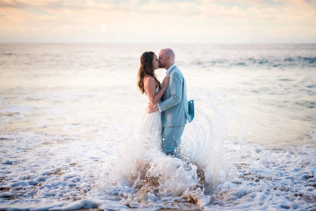 Couple kissing in water for trash the dress.